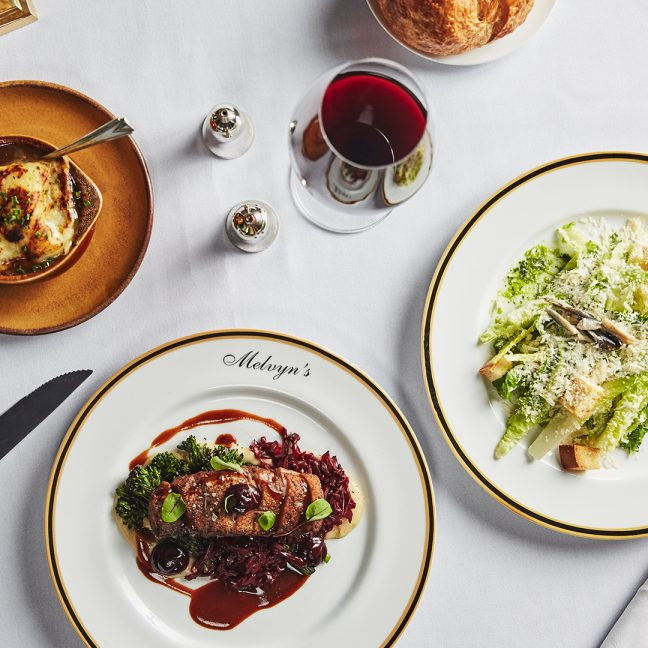 Melvyn's variety of dishes including cesear salad and steak paired with red wine